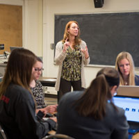 Professor instructs students working on their computers.